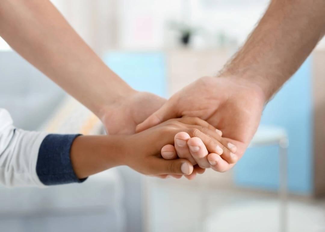 Auslandsadoption - Adoptivkind hält Hände der Eltern